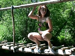 Natural chick squats down on the cross over almost pee shamelessly outdoors